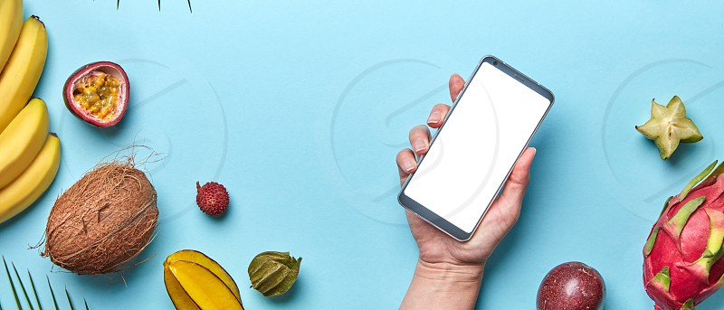 A variety of tropical fruits and a female hand with a phone on a blue background with copy space. The concept of buying products on the Internet. Flat lay photo