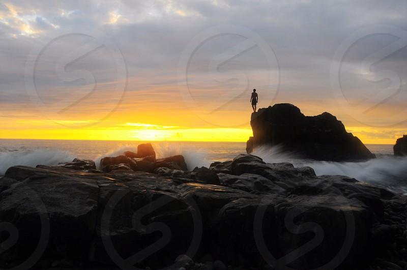 man standing on rock on sunrise view photo