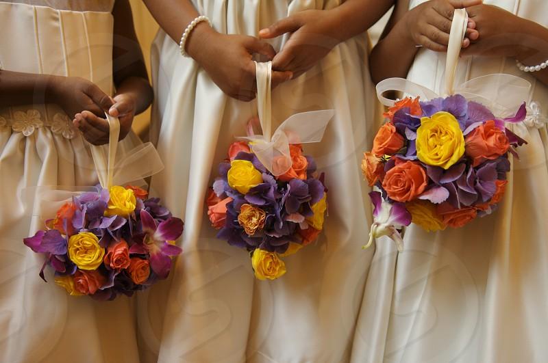 Three flower girls holding floral arrangements photo