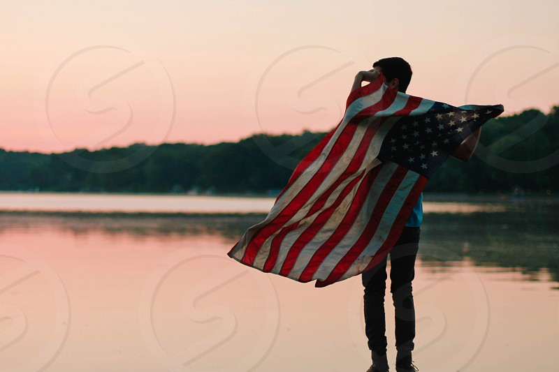 person holding american flag near body of water photo