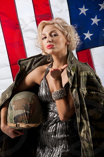 Young blonde in army jacket on an American flag photo