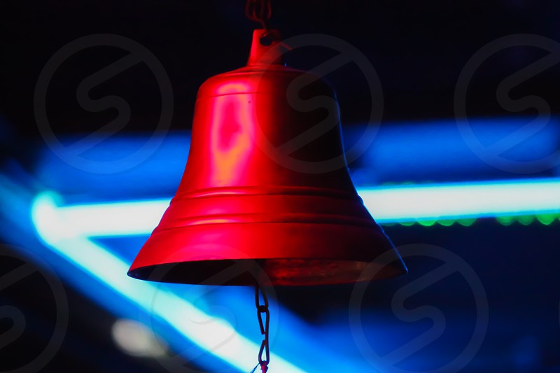 A red bell against blue neon light. photo