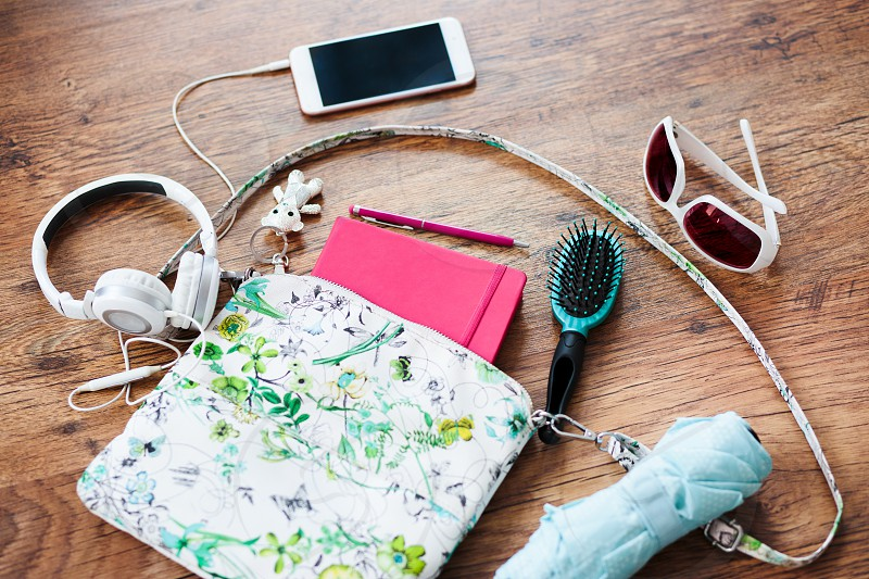 Smartphone sunglasses headphones umbrella and other things pulled out of handbag put on a wooden table. Female stuff. Shot from above photo