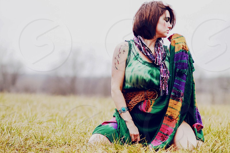 woman in green tie dye batik dress sitting in the grass photo