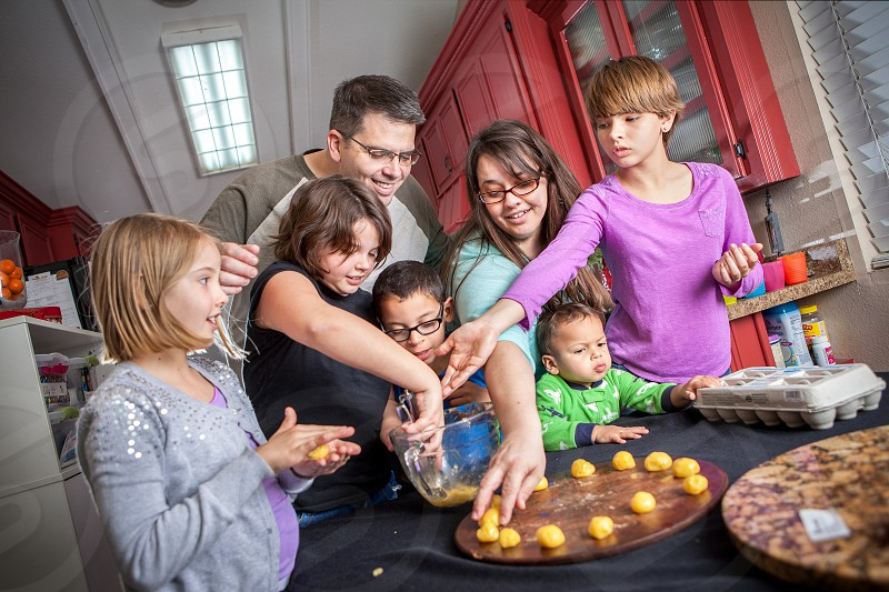 An actual diverse foster home passionate about fostering adopting loving teaching children who need a forever family. Black white mixed race happy learning kitchen table cloth blue grey purple teal green red glasses boys girls woman man yellow relating connecting together diversity. Cooking backing bowl eggs mixing food snack treat cookies dough wooden spoon. photo