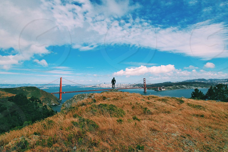 a person standing in the edge of the cliff look at a the golden state bridge and blue white cloudy calm sky during daytime photo