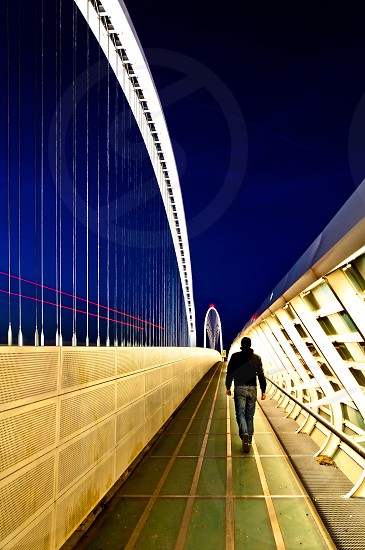 man walks on famous bridge by architect Santiago Calatrava in Reggio Emilia - Italy photo