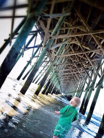 baby standing below the bridge photo