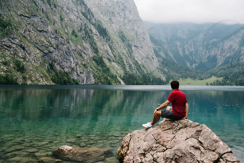 Man sitting on rock looking at beautiful and misty lake in the alps. Obersee photo