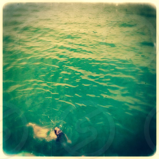 Little girl swimming in lake photo