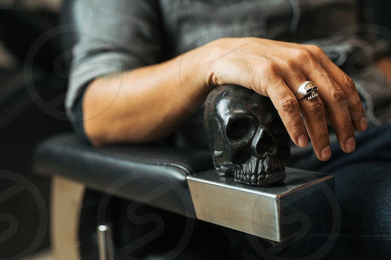Retro style man sit on the chair and hold skull with scissors. - Image photo