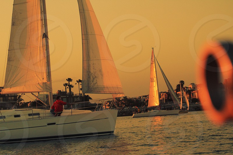 peron in red shirt on white sailboat during golden hour photo