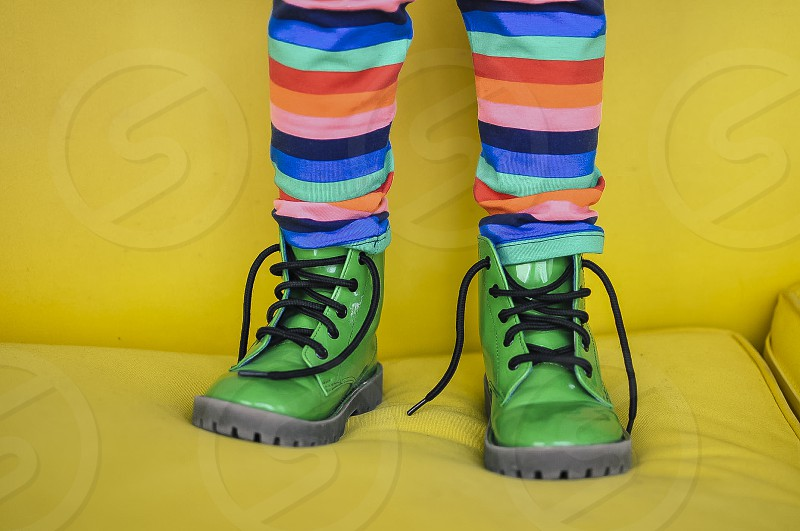 child wearing pair of green patent leather boots standing on yellow sofa photo