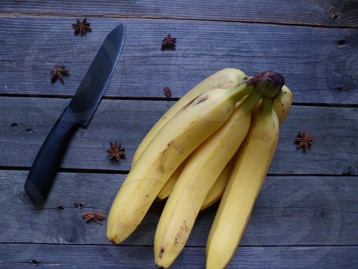 yellow banana fruits beside black steel kitchen knife photo