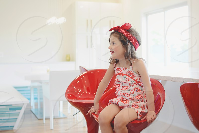Girl on red chair in kitchen  photo