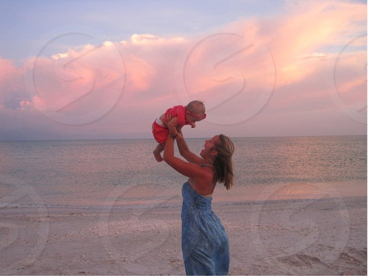 woman carrying a baby on seaside photo