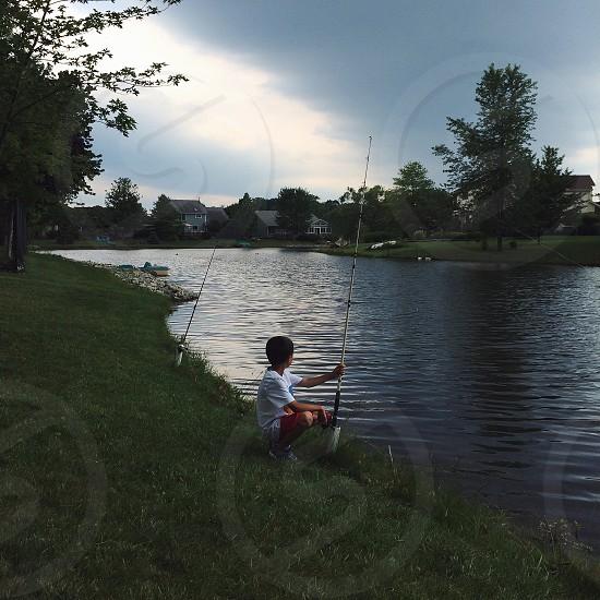 view of boy holding fishing rod photo