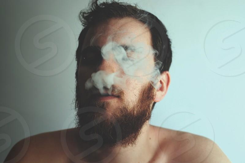 person with black beard puff a smoke photo