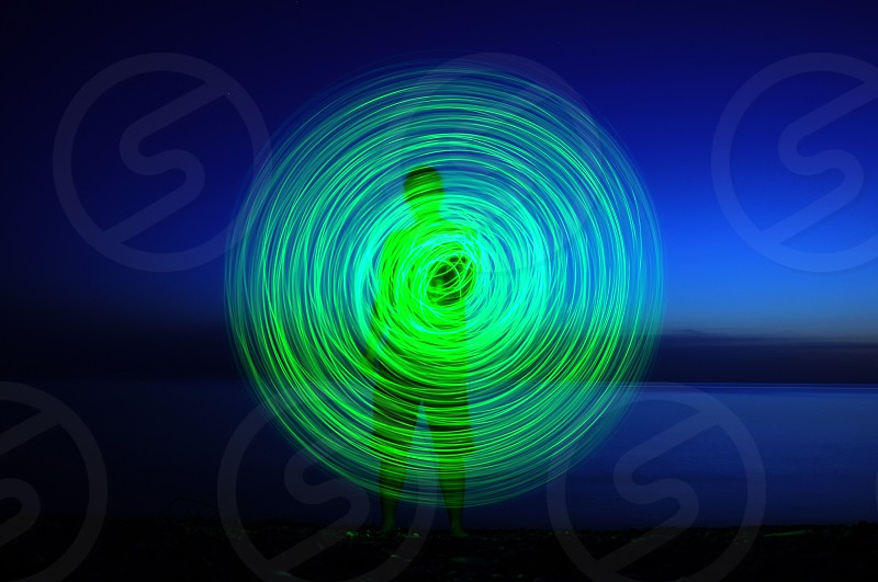 person showing green circular light in time lapse photograph photo