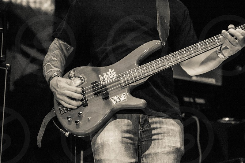 man with tattoo sleeve playing guitar photo