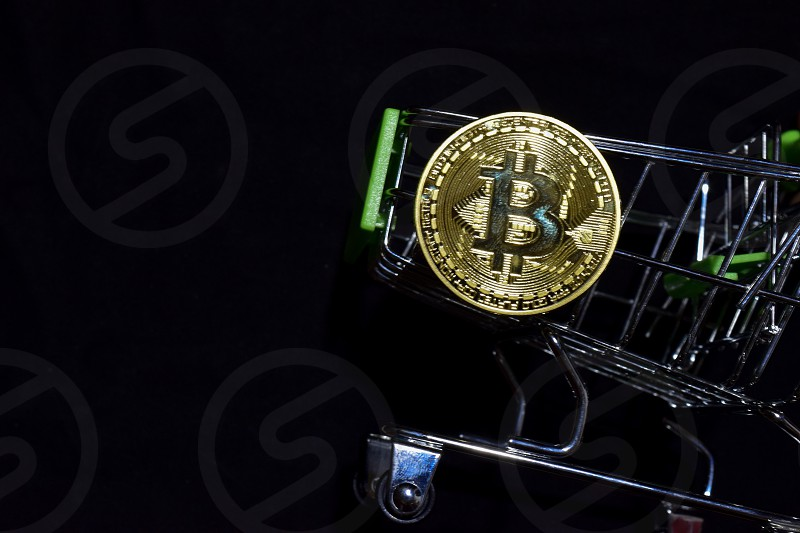 Bitcoin gold and shopping cart on black background. Bitcoin outside a shopping cart. Business concept photo