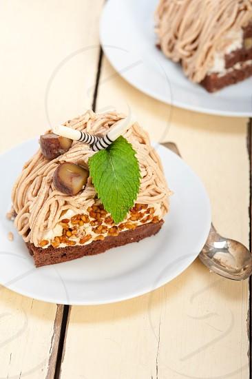 fresh baked chestnut cream cake dessert over rustic white wood table  photo
