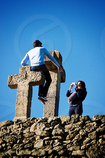 man sitting on top of a stone cross while a woman takes a photo photo