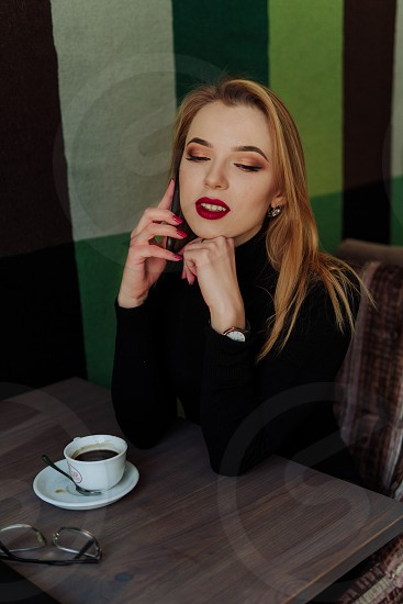 Young beautiful business woman talking on the phone and drinking coffee photo