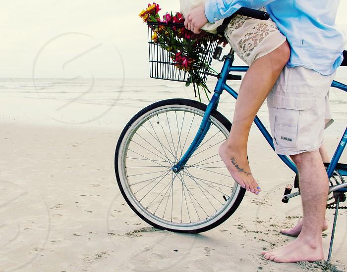 Couple on a bike on the beach. photo