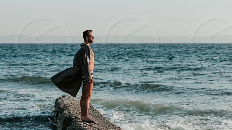Young man in a bathrobe on the beach in sunset photo