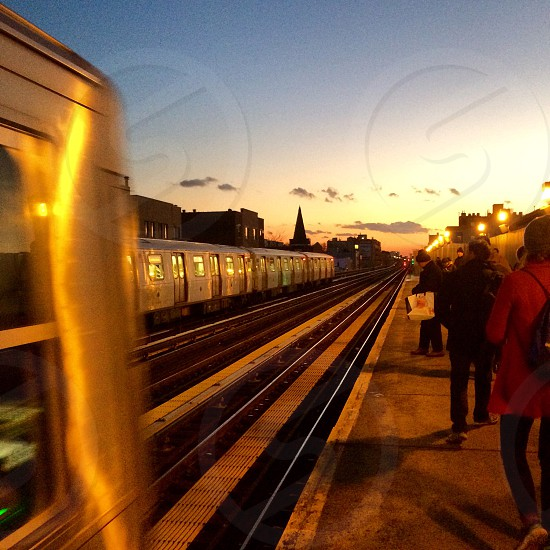 gray train and person walking the subway with during golden hour photo