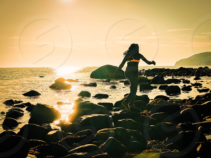 Life energy happy happiness nature girl sunlight backlight  nature ocean jumping stones silhouettes human purity freshness air photo