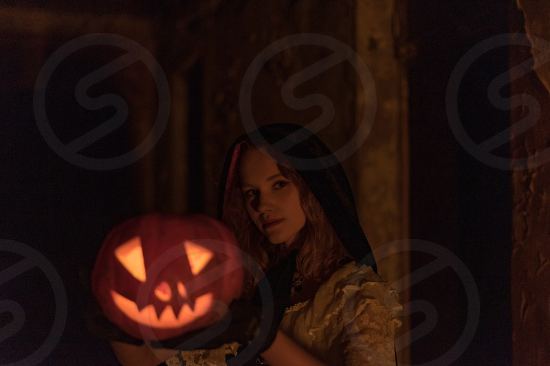Close up portrait of young female caucasian model in vintage dress and vampire cloak holding out scary halloween pumpkin glowing from inside in the dark photo