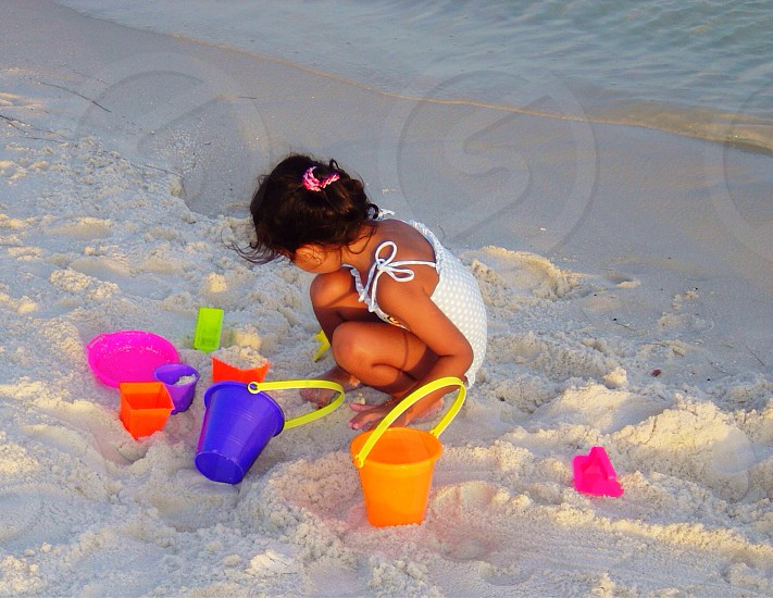 youth girl beach playing on beach sandcastle beach buckets sand kid playing fun photo