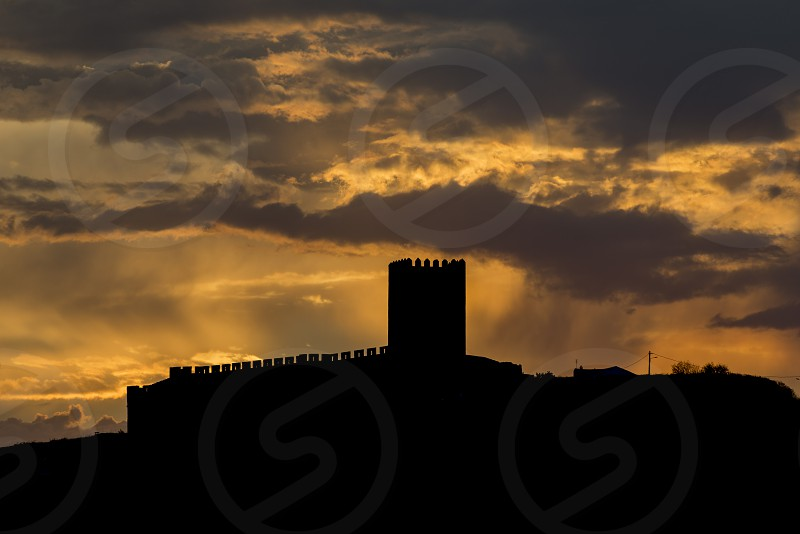 sunrays from the clouds over the catle of portel in portugal photo
