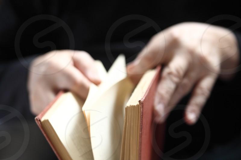 An older man leafs through an old book. photo