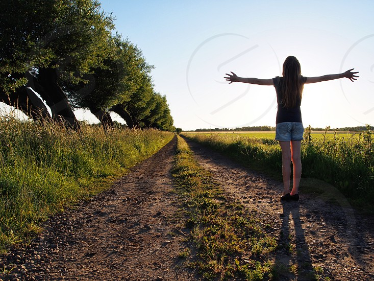 woman raising arms side ward while standing on dirt road photo