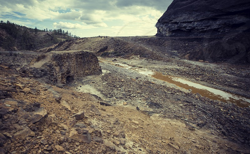 Old stone wall on the banks of the red river (Riotinto) of acid waters with a low pH produced by minerals Spain photo