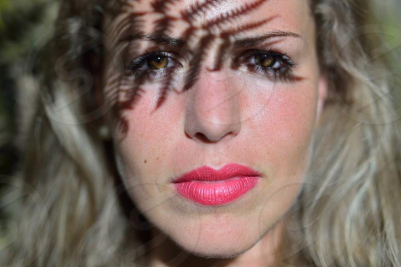 Woman face with fern leaf shadow photo