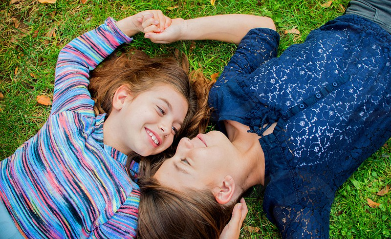 woman in blue floral button up long sleeved shirt staring and lying on green grass beside girl smiling photo