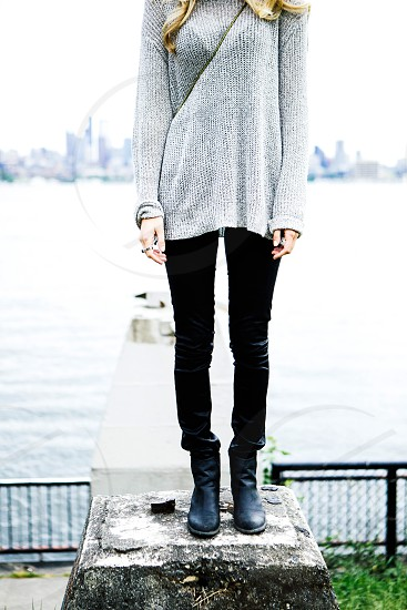 woman in grey long sleeved shirt and black pants standing photo