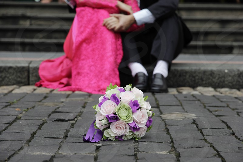 Bride and Groom with wedding paper flower Location: On street photo