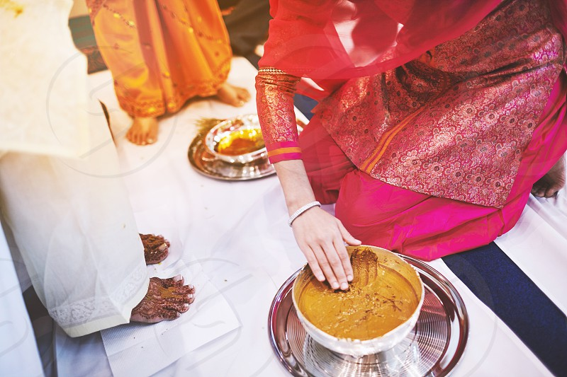 The bride standing on the white fabric and the women prepraing the turmeric (haldi) oil mixed with milk to pasting on the bride's feet and body the traditional rituals of indian marriage ceremony photo
