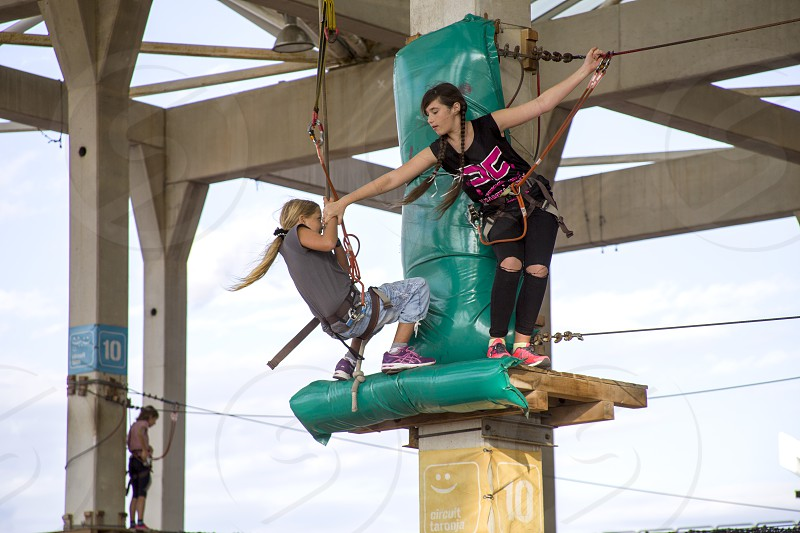 Girls in an adventure park moves over a suspension bridge photo