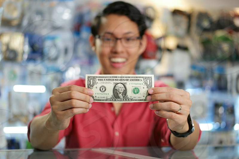 first dollar money shop showing bill business asian aspirations beginnings businessman cheerful chinese clerk computer concepts confident currency earn earnings entrepreneur finance front view happy holding job looking at camera male man new business occupation one person owner people portrait pride retail sale sales self-employed small business smile smiling store success symbol wealth work working young photo