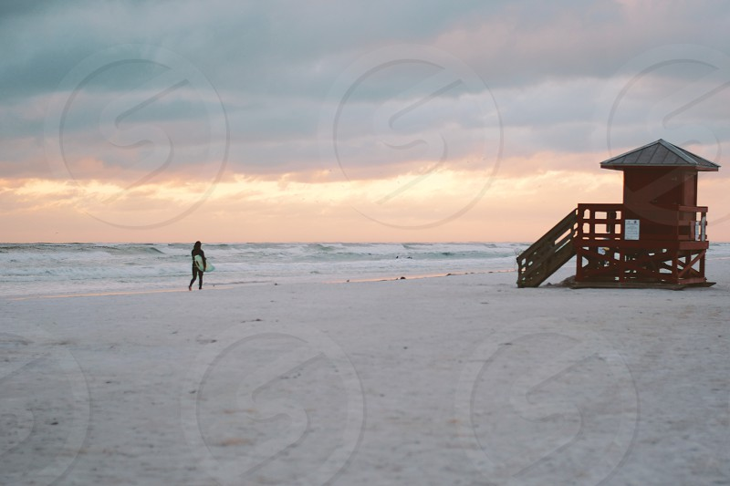 person holding surfboard standing on beach near ocean  photo