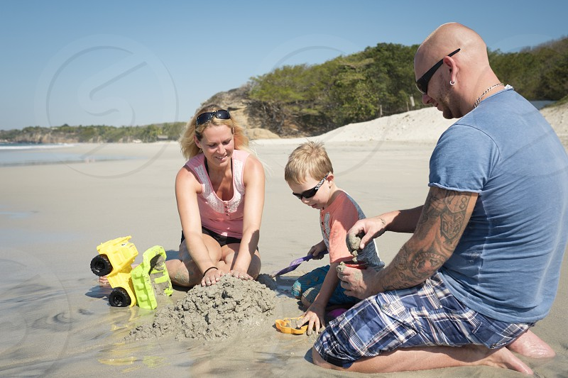 Family of 3 playing in the sand on the beach Father mother toddler son. Riviera Nayarit Mexico photo