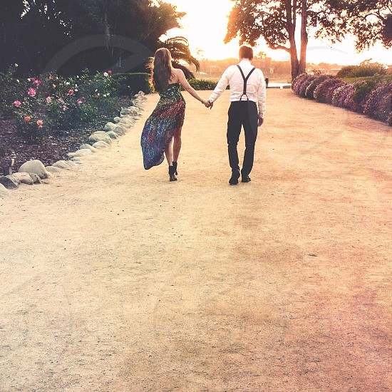 man in white and black formal suit outfit holding hand of woman in green black and red spaghetti strap dress walking at brown sand between flowers during orange sunset photo