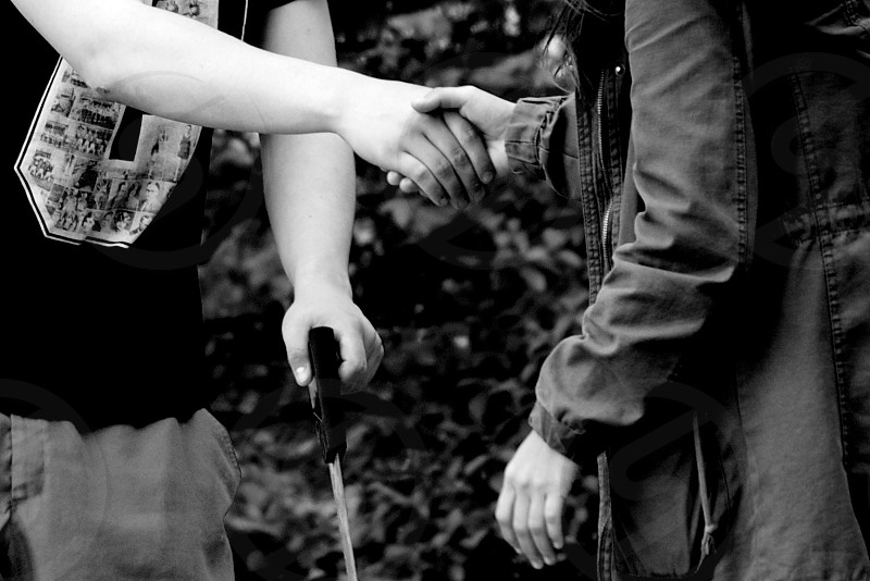 person in grey jacket shaking hands with a person photo