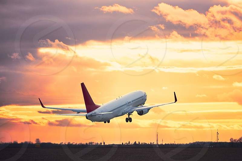 Airplane taking off from the airport runway at the sunset. photo